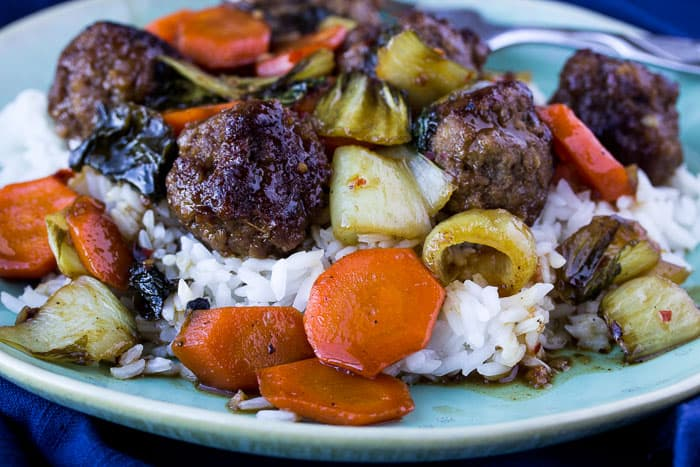 Orange-Glazed Meatballs with Bok Choy and Jasmine Rice on a Green Plate