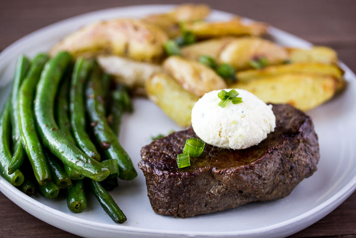 Sirloin Steak, Blue Cheese Compound Butter, Green Beans, and Potatoes on a Gray Plate