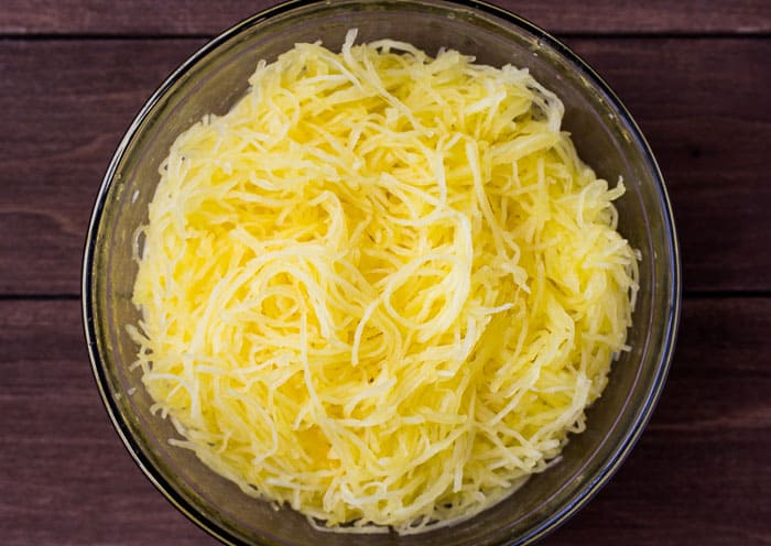 Cooked Spaghetti Squash In a Bowl over a wood background