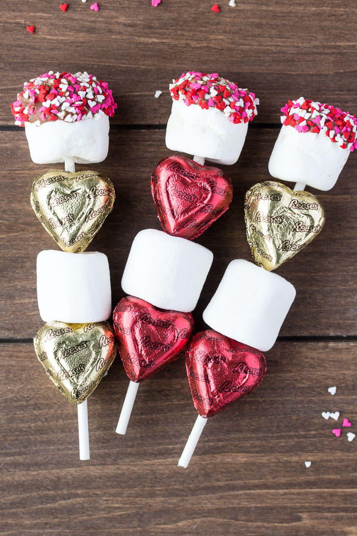 3 Valentine's Day Candy Kabobs on a wood background with heart sprinkles scattered around