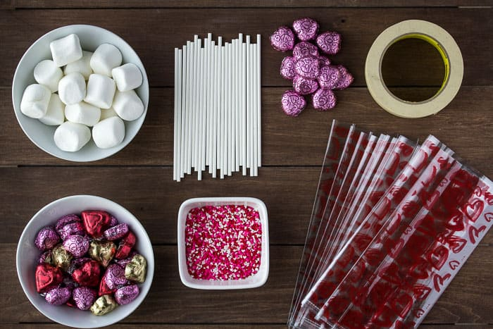 All of the Supplies Need to Make the Candy Kabobs layed out on a wood background