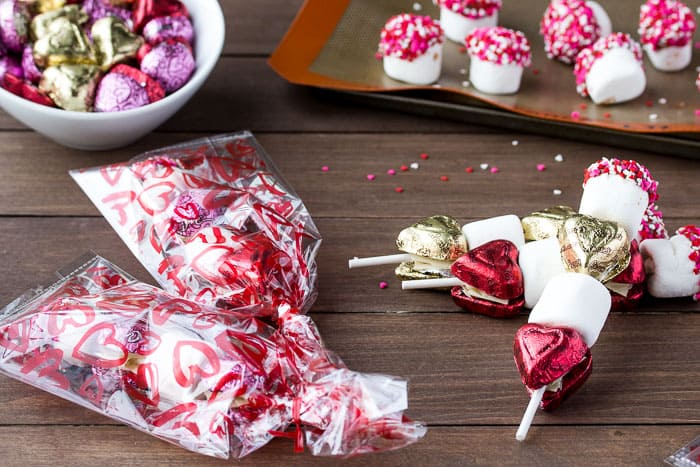 2 Valentine's Day Candy Kabobs in Gift Bags, 2 not in gift bags with extra candy and chocolate dipped marshmallows in the background all on a wood surface with extra sprinkles scattered around