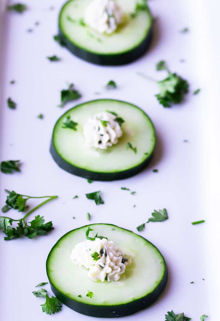 3 cucumber slices topped with herbed cream cheese on a white serving tray