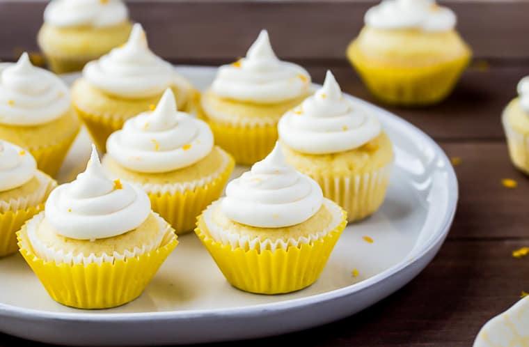 Mini Lemon Cupcakes on a white tray over a wood backdrop