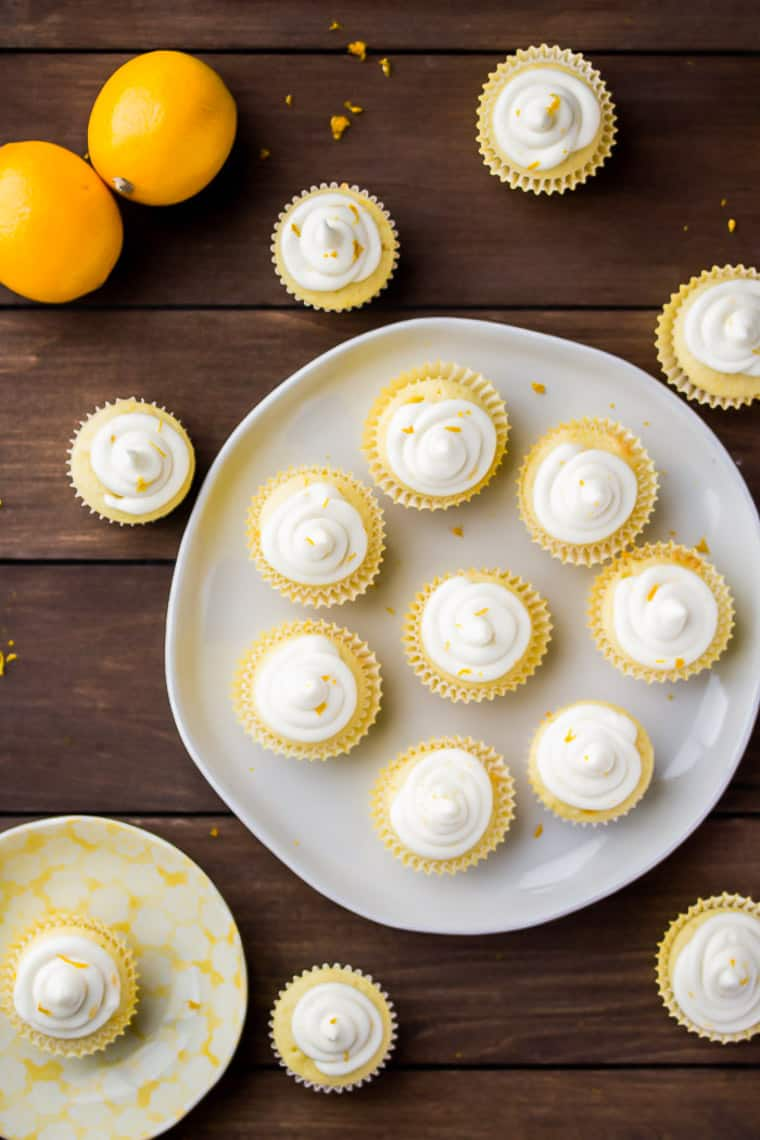 Overhead view of Mini lemon cupcakes on a white round tray with cupcakes scattered around it and 2 lemons all over a wood background