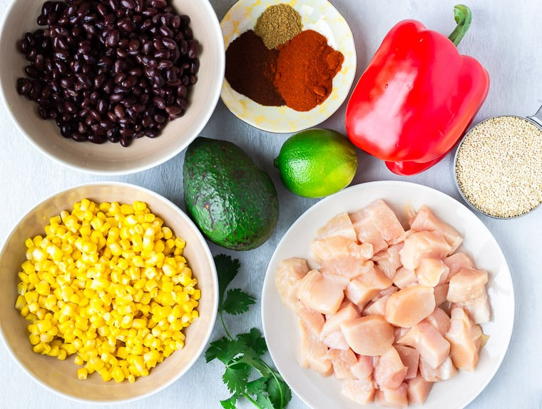 Ingredients needed to make southwestern chicken and quinoa in bowls or sitting on a white background