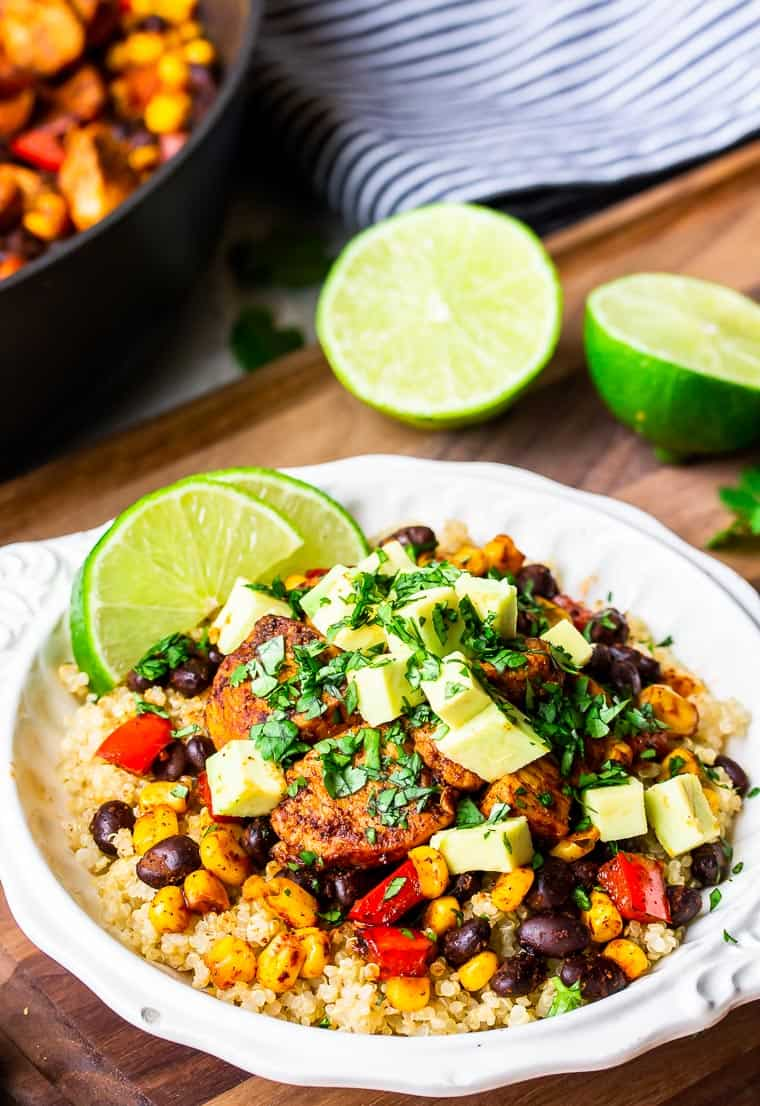 A white bowl filled with quinoa, chicken, black beans, corn, red pepper, avocado, and lime slices on a wood board with 2 lime halves, a blue and white towel and part of a skillet in the background