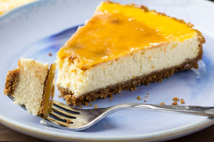 A Slice of Vanilla Orange Cheesecake with a Bite on a Fork