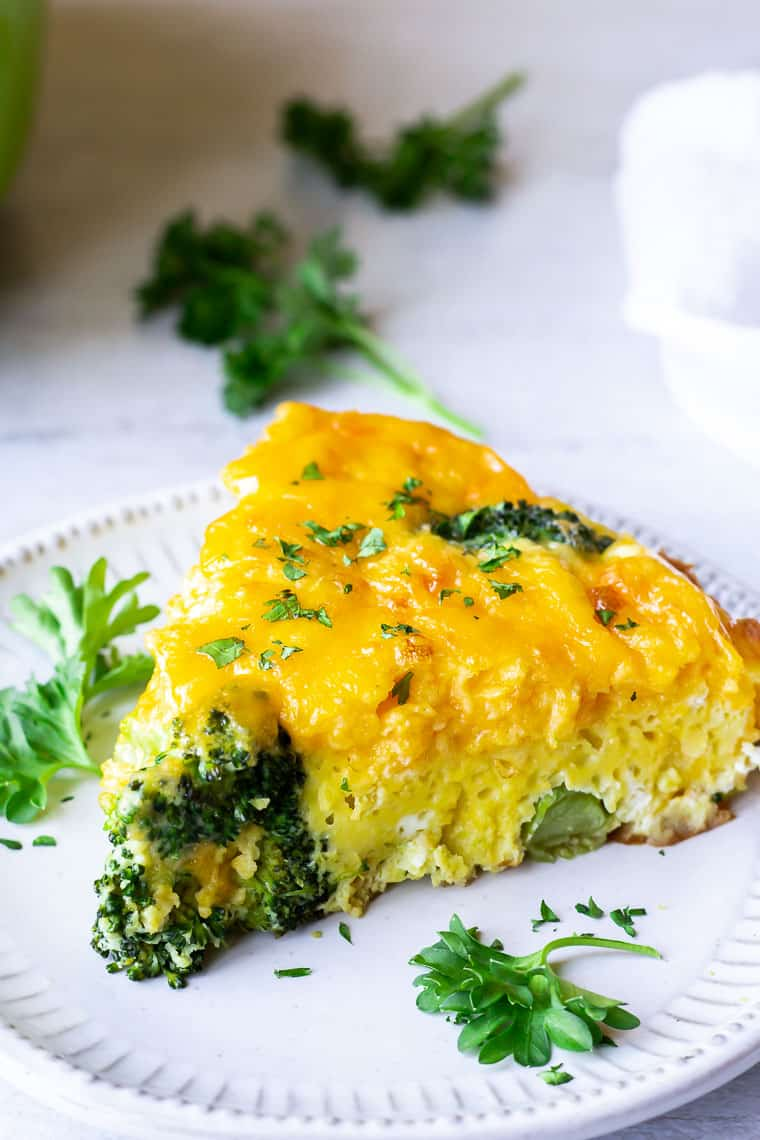 Close up of a slice of broccoli cheddar frittata on a white plate with parsley in the backrground