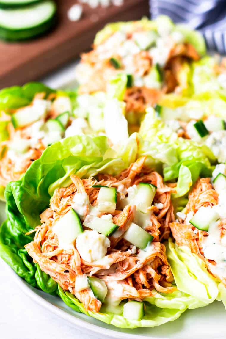 Close up of a Buffalo Chicken Lettuce Wrap on a white plate with more wraps blurred in the background with a cutting board, cucumber slices, blue cheese, and a blue and white towel.