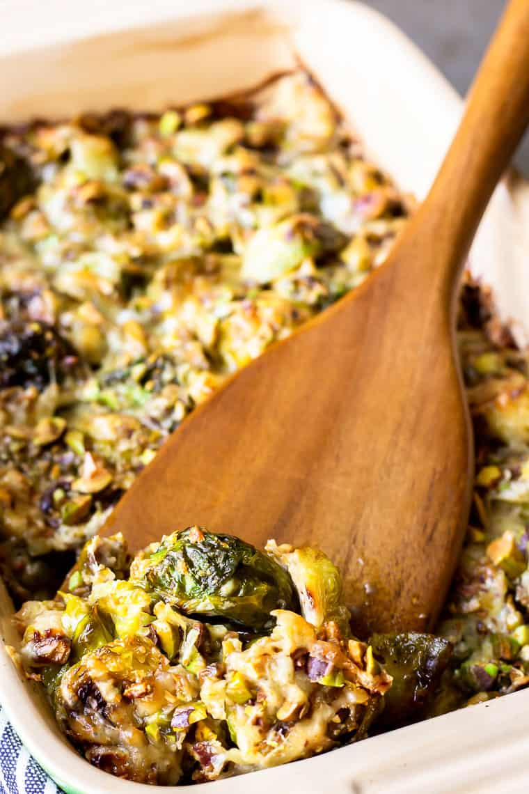A scoop of Brussels Sprouts Gratin being lifted up with a wood server