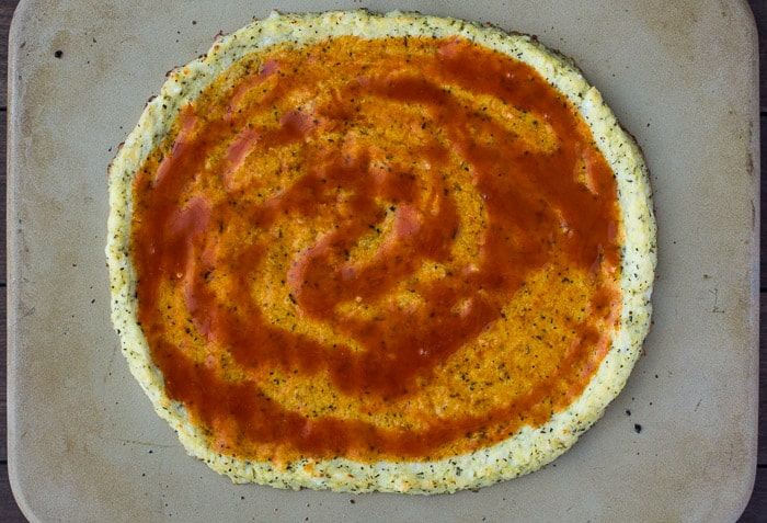 Buffalo Sauce Spread Onto The cauliflower Pizza Crust on a pizza stone