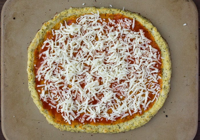 Cauliflower Pizza Crust with Buffalo sauce and Cheese Added on a pizza stone prior to baking
