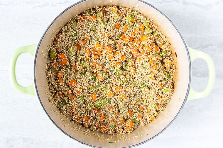 Quinoa and vegetables cooking in a light green dutch oven over a white background