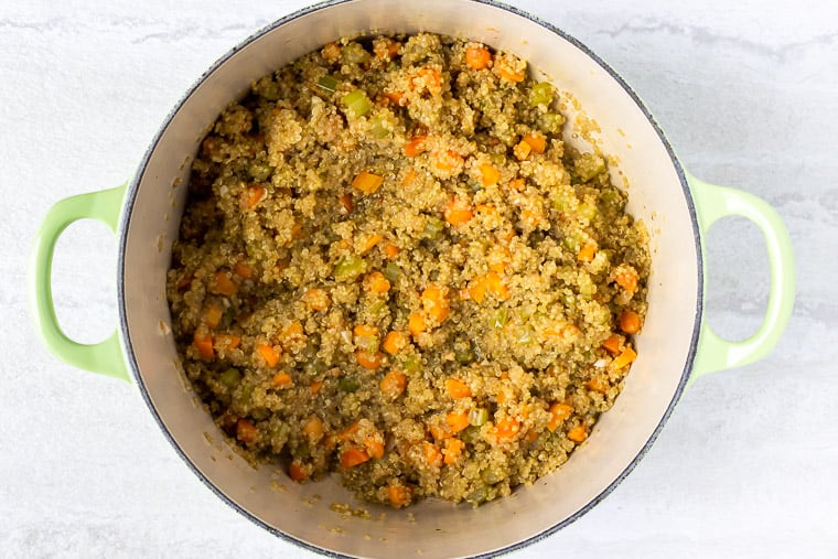 Cooked quinoa and vegetables in a light green dutch oven over a white background