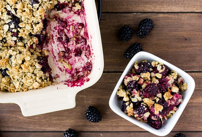 Blackberry Crisp in a Baking Dish with a Single Serving on a Wood Back Drop