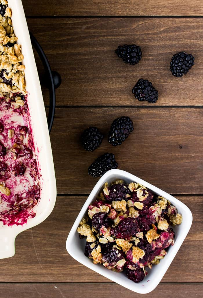 A Bowl of Blackberry Crisp with Blackberries on a Wood Board