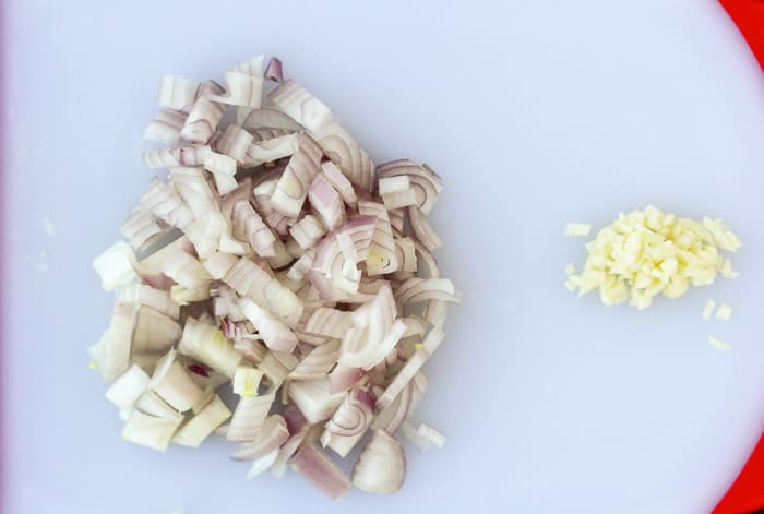 Chopped Shallot and Minced Garlic on a White Cutting Board
