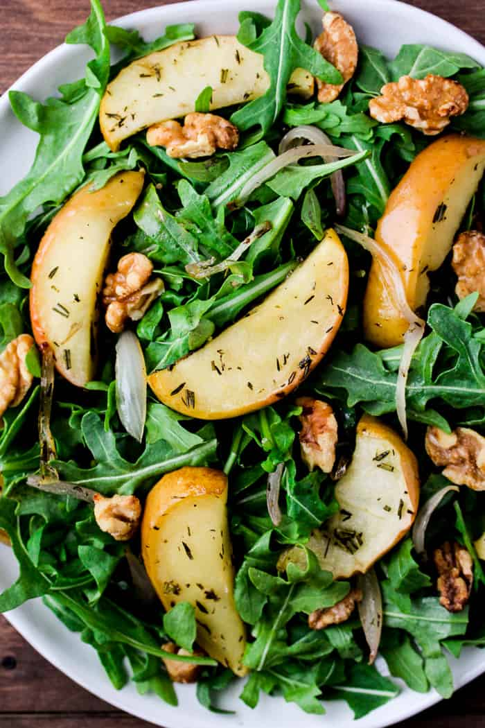 Close up of Roasted Apple Arugula Salad on a Large White Plate