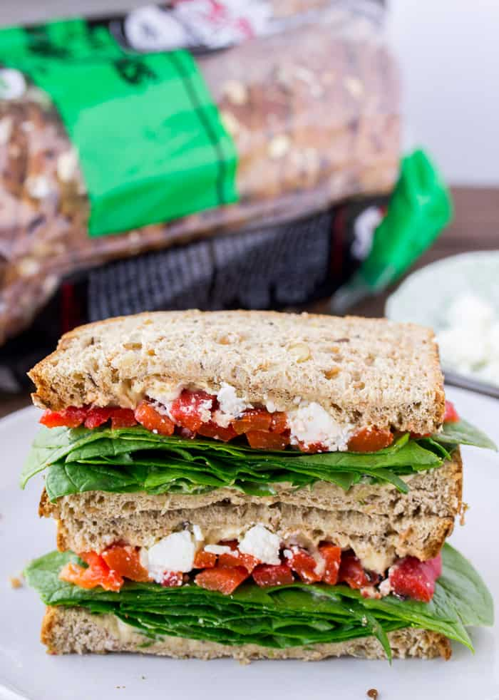 2 halves of a spinach sandwich stacked on top of each other with a bag of bread in the background a small green plate