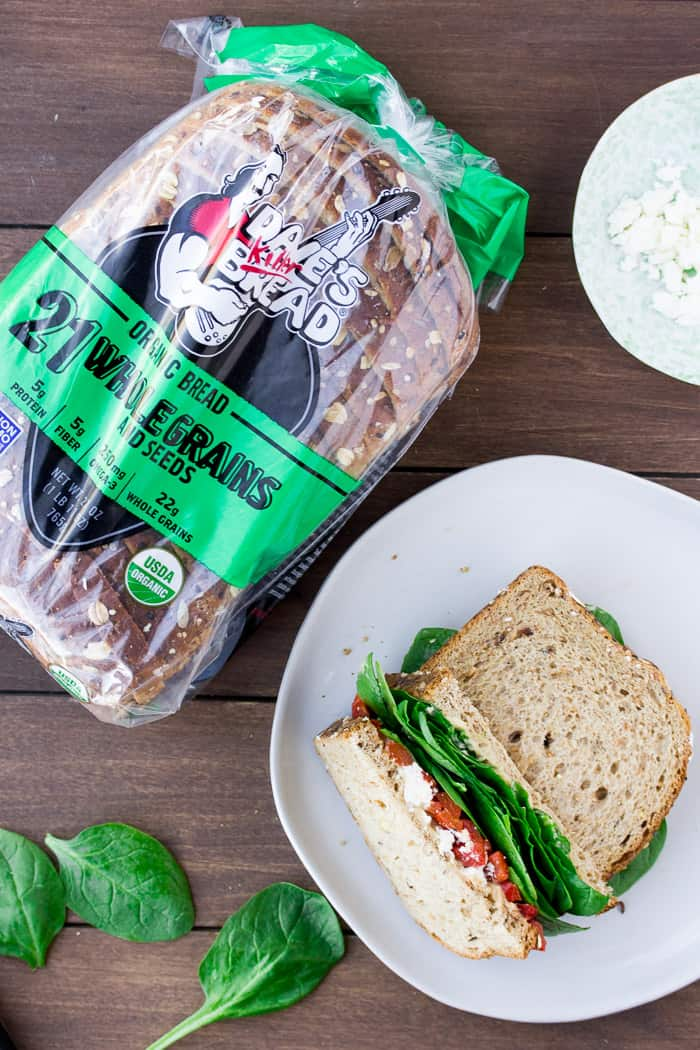 A Roasted Red Pepper Sandwich with a Bag of Dave's Killer Bread on a Wood Back Drop