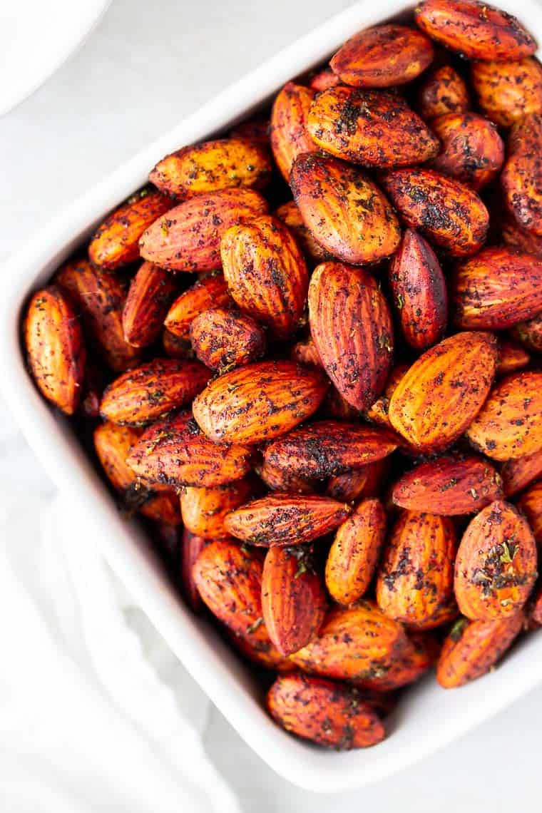 Close up of Chipotle Chili Lime Almonds in a white square bowl over a white background