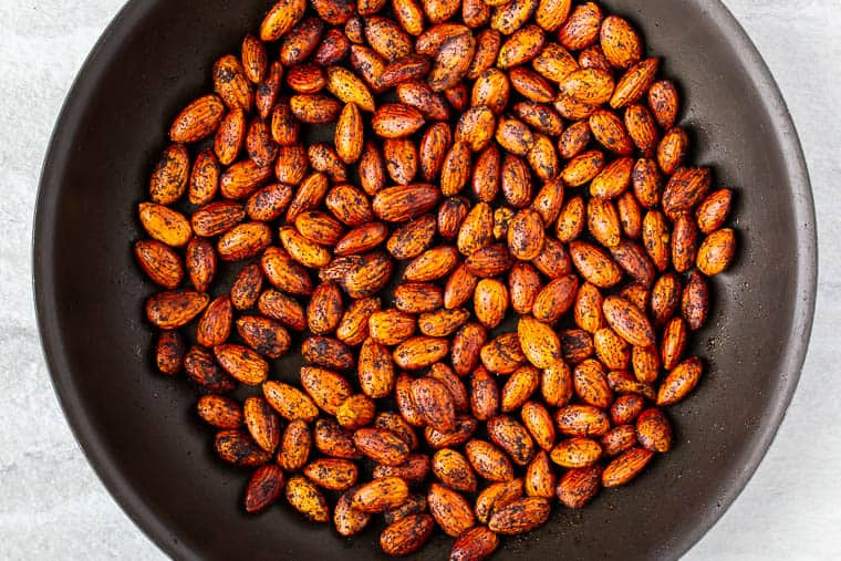 Almonds and chipotle chili powder cooking in a black skillet over a white background