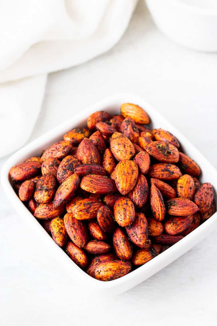 Chipotle Lime Almonds in a square bowl on a white background with a white towel and a white bowl in the background
