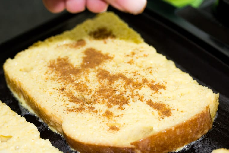 Close up of a piece of French Toast on a Griddle with Cinnamon Being Sprinkled on Top