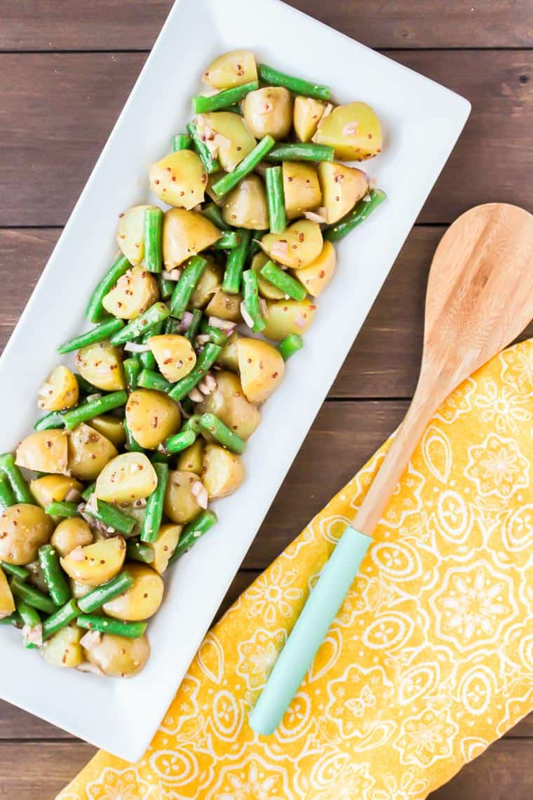 Green Bean Potato Salad on a Rectangular Serving Tray with a Yellow Napkin and Wooden Spoon