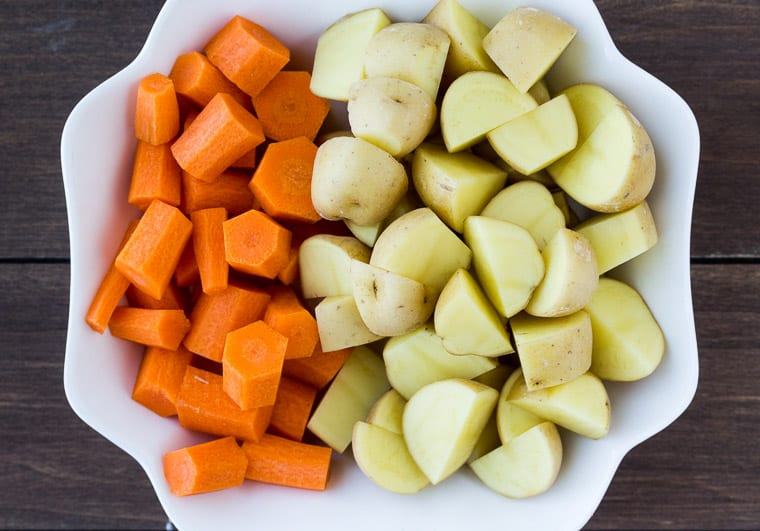 Cut Potatoes and Carrots in a White Bowl over a wood background