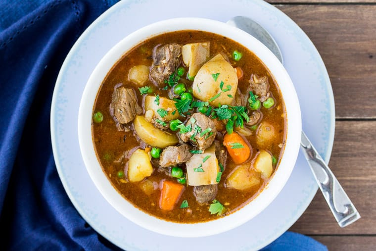 Instant Pot Beef Stew from Overhead in a white Bowl with a Blue Napkin