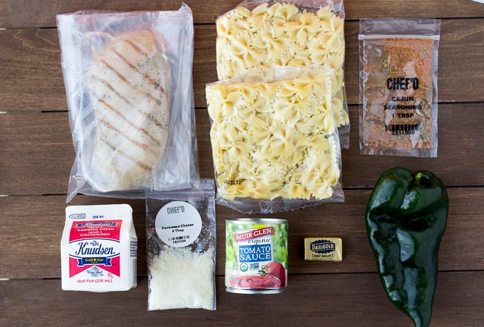 Ingredients for the Chef'd Cajun Chicken Pasta on a Wood Board