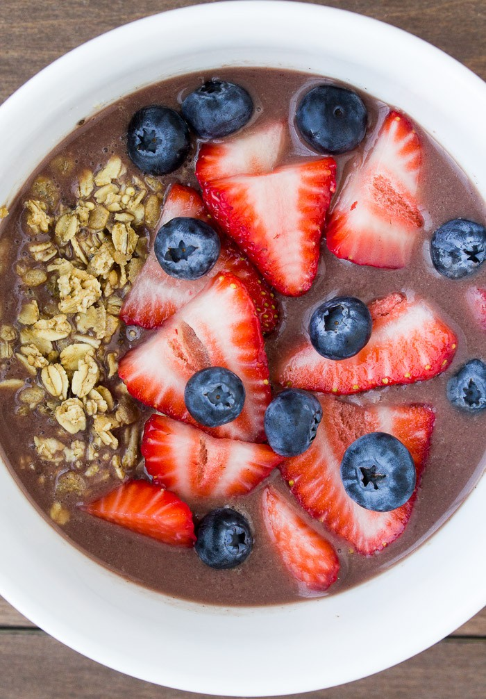Overhead View of the Acai Bowl Topped with Strawberries, Blueberries, and Granola in a White Bowl