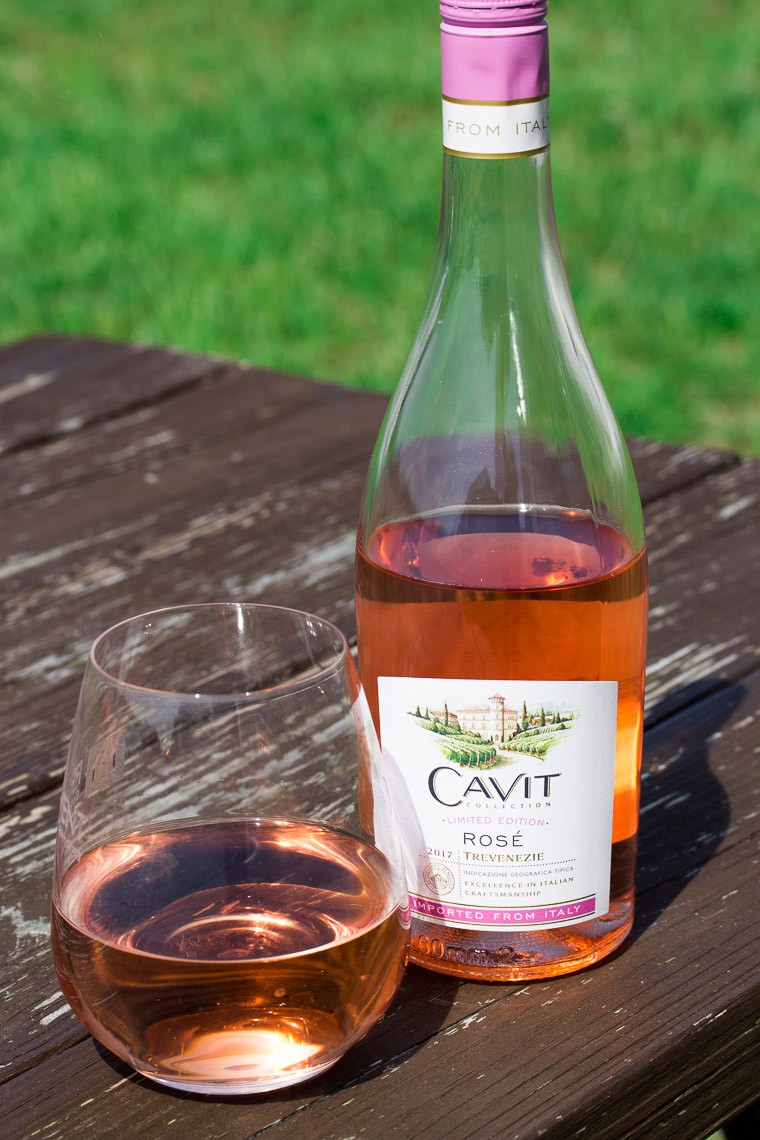 A Bottle and Glass of Cavit Rose on a Weathered Wood Table with Grass in the Background
