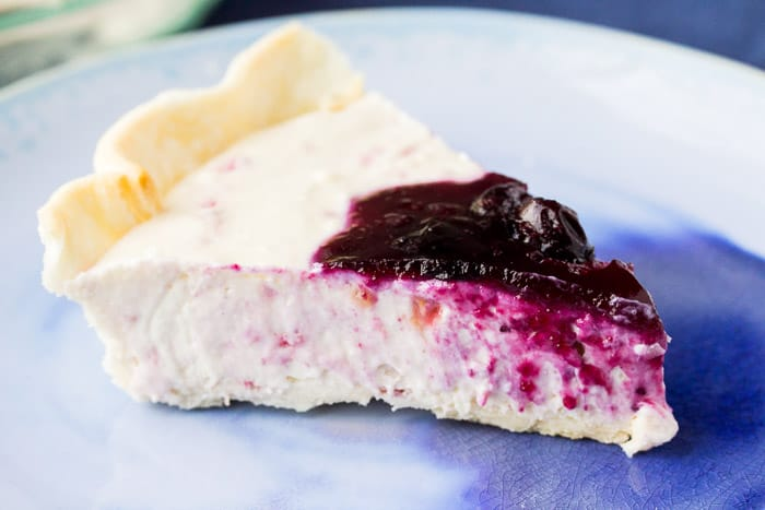 A Slice of Raspberry Cheesecake in a Pie Shell on a Blue Plate
