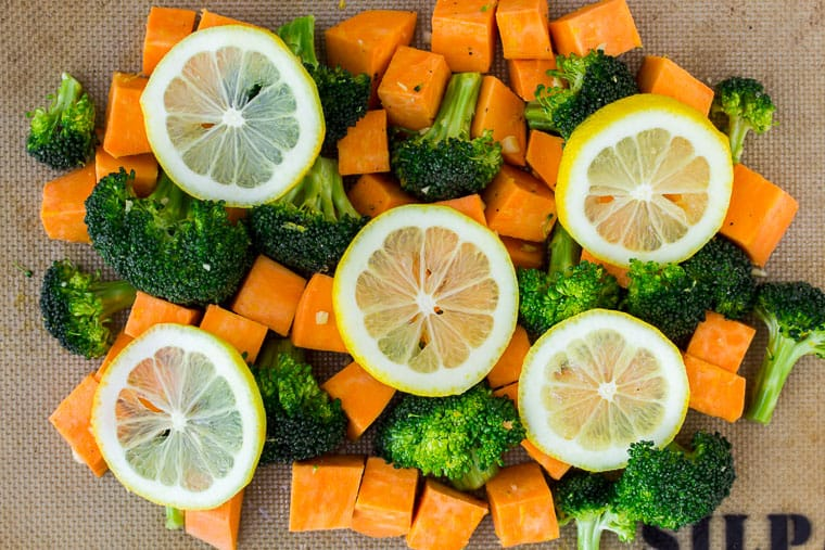 Cubed Sweet potatoes and broccoli on a silpat baking mat with lemon slices on top