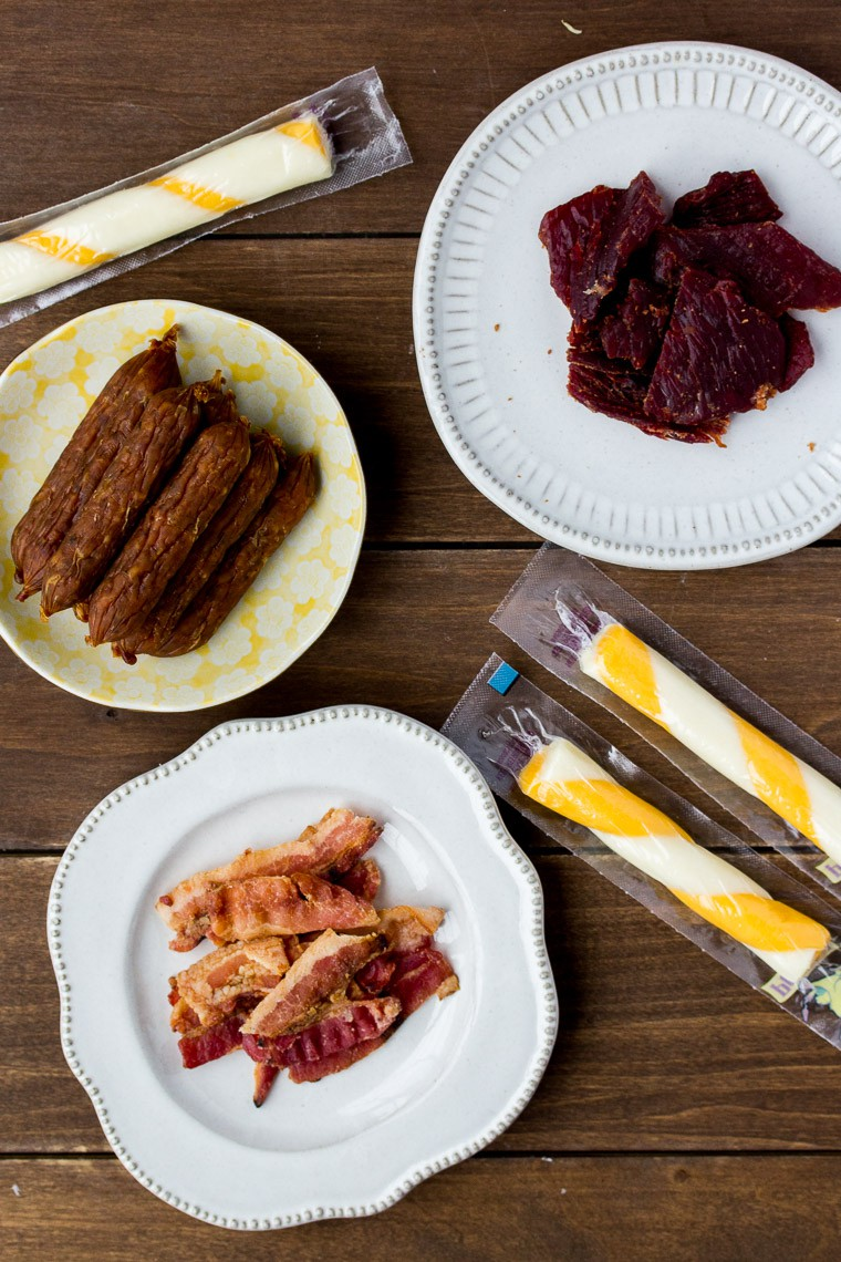 Different Types of Beef Jerky and Cheese Sticks on a Wood Back Drop