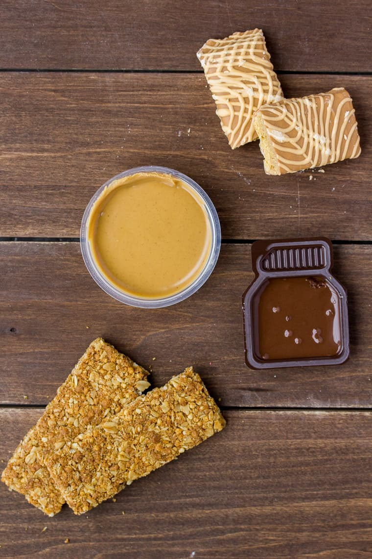 Different Granola Bars with Cups of Peanut Butter and Chocolate Hazelnut Dip