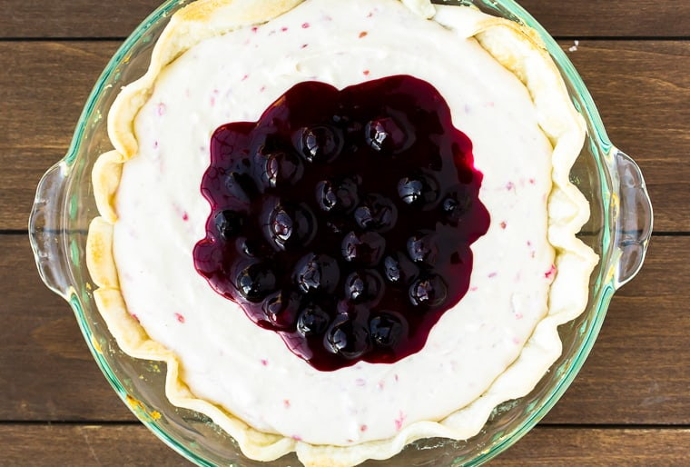 No Bake Raspberry Cheesecake topped with blueberry sauce in a pie dish over a wood backdrop