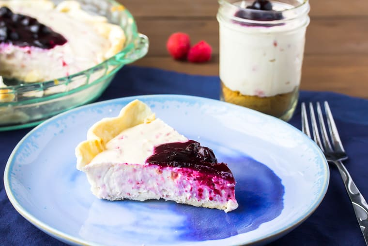 A slice of no bake raspberry cheesecake on a blue plate over a blue napkin with part of the whole pie showing and a mason jar filled with cheesecake, fork, and raspberries in the background