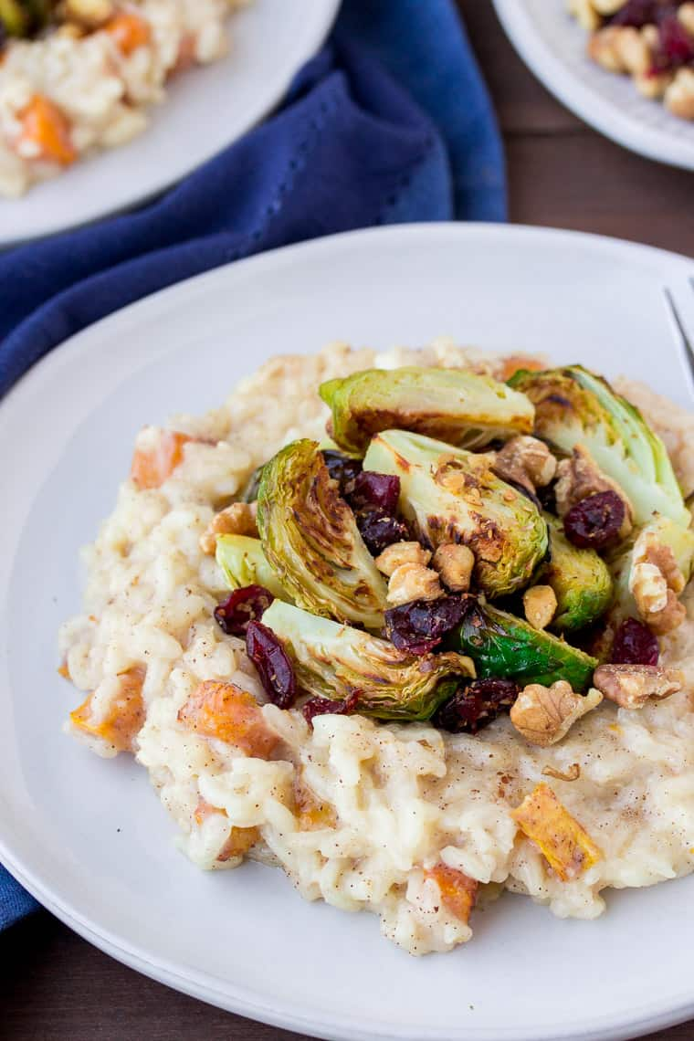 Roasted Butternut Squash Risotto with Brussels Sprouts, Cranberries, and Walnut on a Blue Plate with a Blue Napkin over a wood table