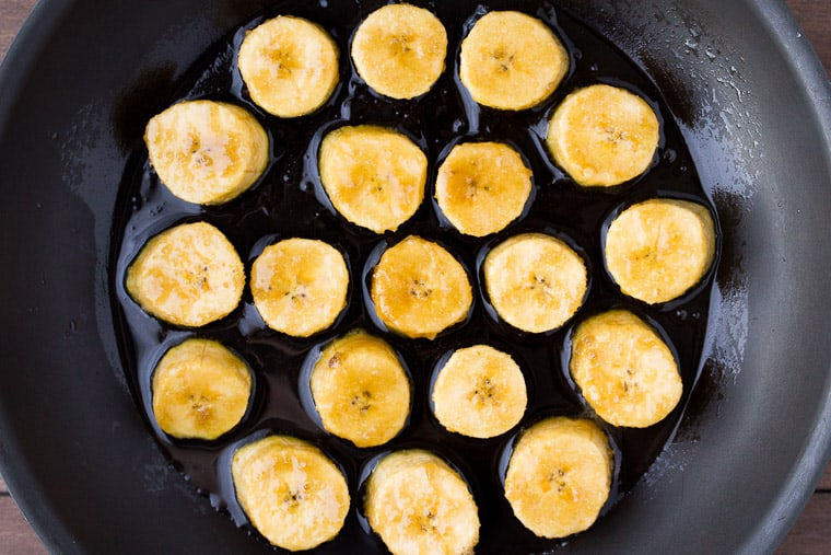 Raw Plantains Cooking in Coconut Oil in a black skillet