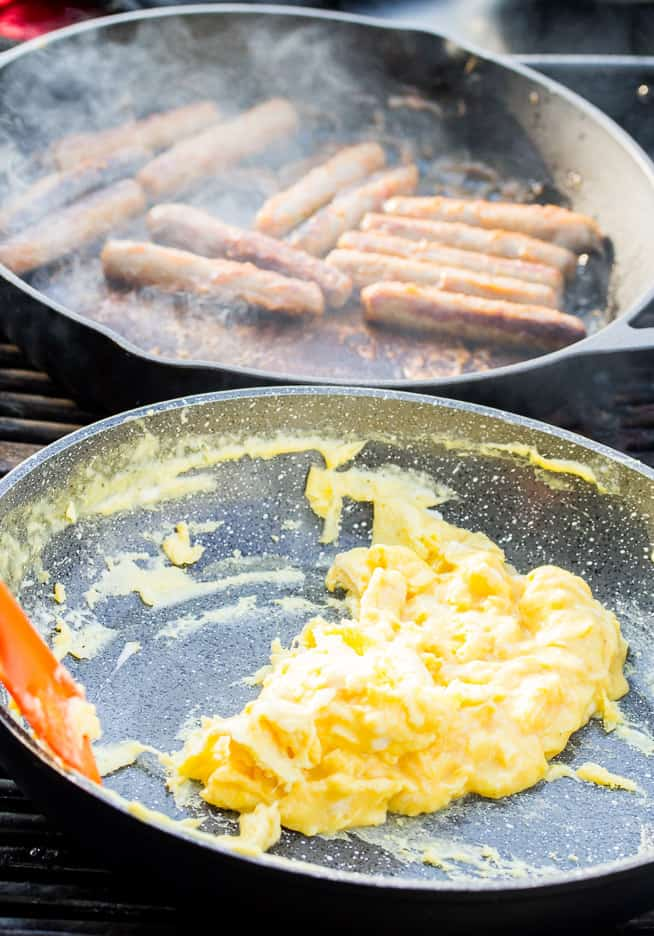 Sausage and Eggs Cooking in Pans on the Grill