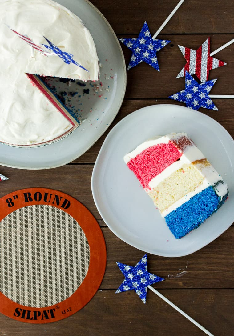 OverHead View of the Red, White, and Blue Cake on a Plate next to the Whole Cake and a Silpat Cake Mat with Patriotic Stars All Around on a Wood Back Drop