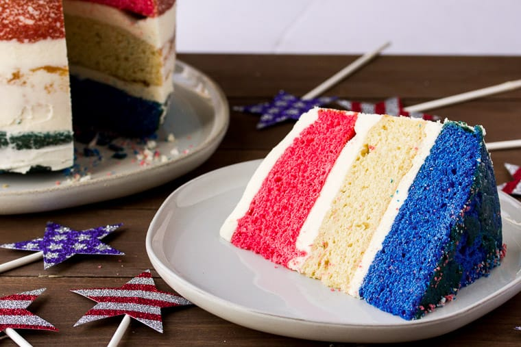 A Large Slice of Red, White, and Blue Cake on a White Plate with the Whole Cake and Patriotic Star Decorations in the back ground