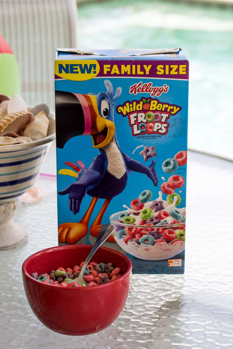 Wild Berry Froot Loops Box with a Bowl of Cereal on a Table Outside with a Pool in the Background To Start our Florida Mornings Every Day!