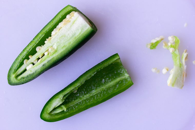 A jalapeno pepper cut in half with some of the seeds and membrane removed and off to the side