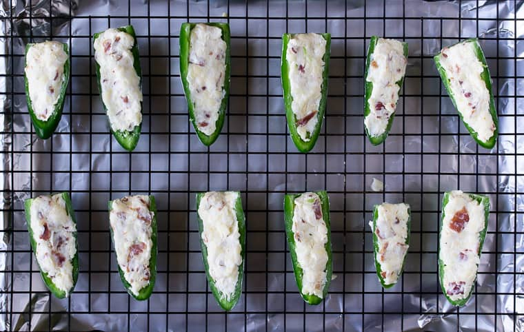 Jalapeno peppers stuffed with cream cheese on a baking rack