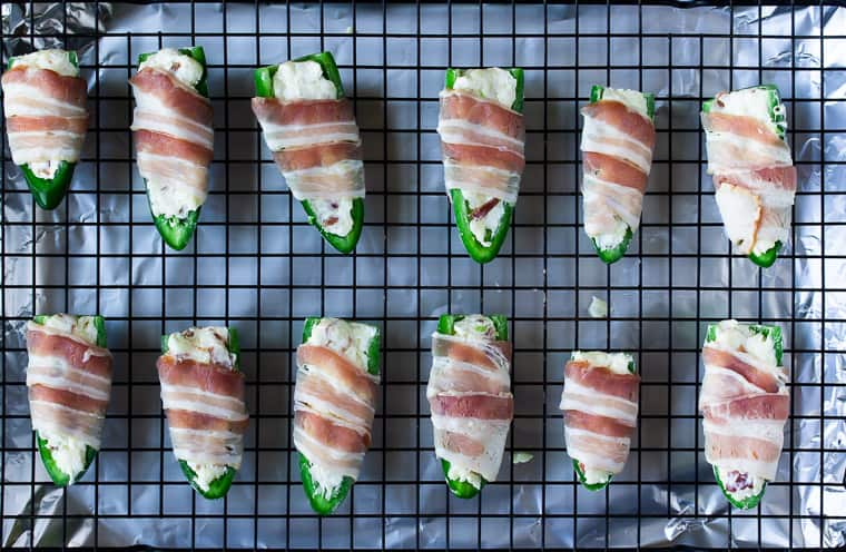 Jalapeno peppers stuffed with cream cheese and bacon, wrapped in bacon on a baking rack